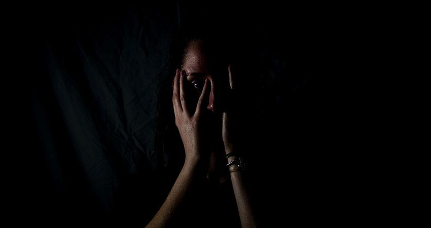 kvinna håller för ansiktet händer en vecka mot våld unsplash.jpg